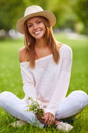 stylish girl: Stylish girl in hat and casualwear sitting on lawn in park Stock Photo