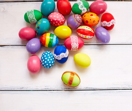 creatively: Creatively painted Easter eggs on white wooden background Stock Photo
