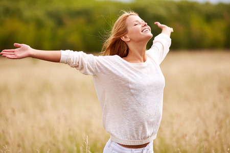 worship praise: Happy young female with her arms outstretched enjoying freedom