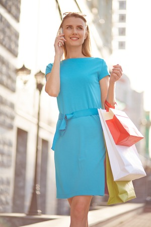 shopaholism: Modern young woman with shopping bags calling outdoors