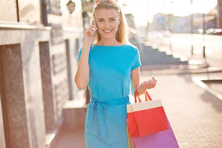 shopaholism: Happy blond girl with shopping bags speaking on cellphone Stock Photo