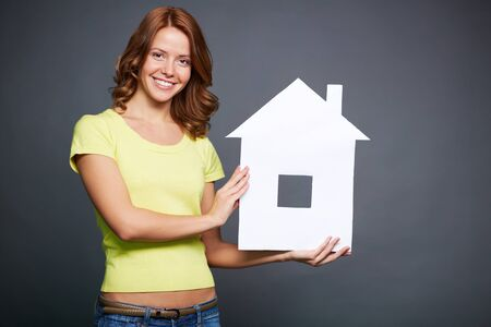 selling house: Happy young woman showing paper house Stock Photo