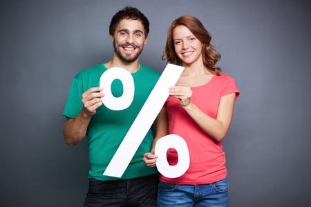 Affectionate couple showing percentage symbol