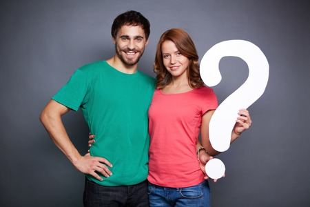 on the mark: Affectionate couple showing paper question mark and looking at camera