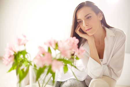 Calm young woman looking at bunch of pink flowers photo