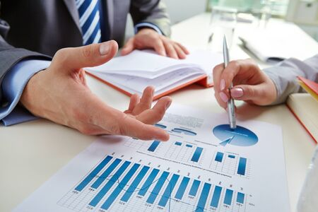 paper work: Businessman pointing at document with chart during discussion with colleague