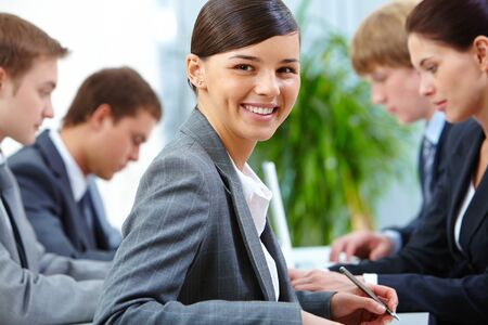 Successful businesswoman looking at camera on background of working colleagues photo
