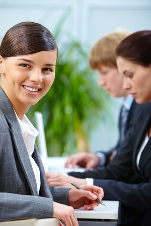 Happy employer looking at camera in working environment photo