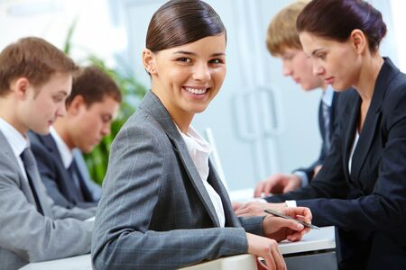 Cheerful manager sitting at workplace on background of working partners photo