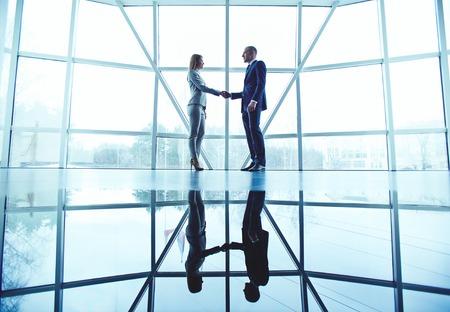 Jonge zakelijke partners handshaking na het maken van overeenkomst