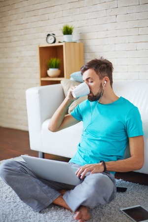 addiction drinking: Handsome guy drinking tea or coffee while using modern gadgets at home