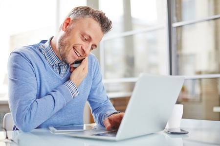 work addicted: Businessman in casual working with latop and speaking on cellphone