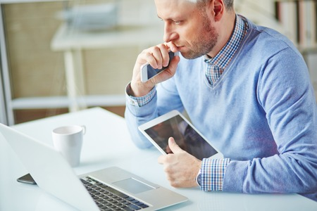 business networking: Pensive businessman working with multi-media gadgets in office Stock Photo