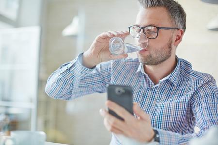 tomando agua: Hombre de negocios en el agua potable casual mientras lee sms o número de marcación en el teléfono móvil