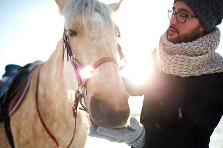 winterwear: Young man in winterwear and his horse