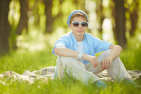 lad: Portrait of cute lad in casual clothes and sunglasses sitting on green lawn Stock Photo