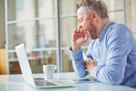 work addicted: Tired man yawning at workplace in office Stock Photo