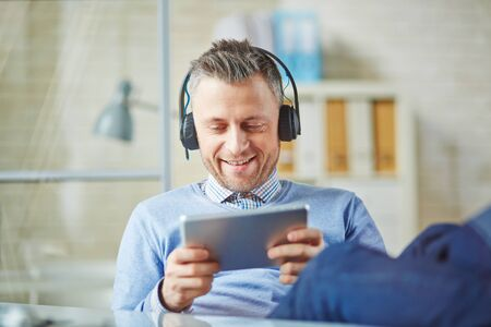 businessman smiling: Happy businessman with earphones using touchpad