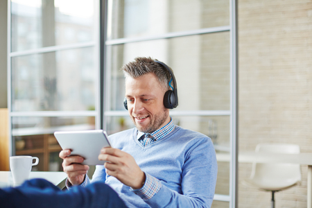 obsessed: Happy businessman with earphones using touchpad in office