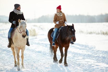 uomo a cavallo: Coppie felici in cavallo winterwear cavallo in ambiente naturale Archivio Fotografico