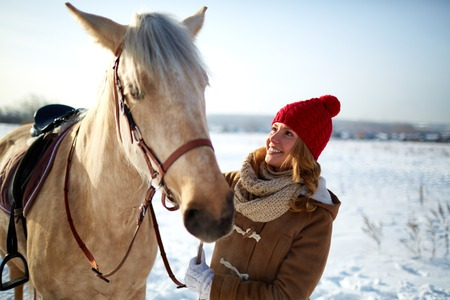 winterwear: Happy girl in winterwear looking at horse in rural environment