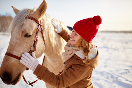 winterwear: Young female in winterwear looking at horse Stock Photo
