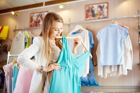 shopaholism: Beautiful young woman trying new elegant dress