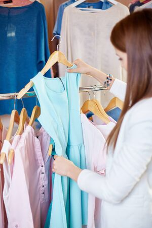 shopaholism: Beautiful young woman looking through new clothes collection