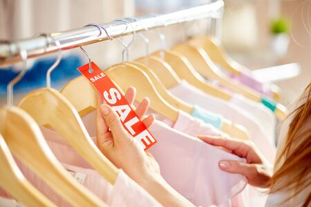 shopaholism: Female hand holding sale label between hangers with clothes