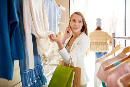 shopaholism: Beautiful young shopper speaking on the phone Stock Photo