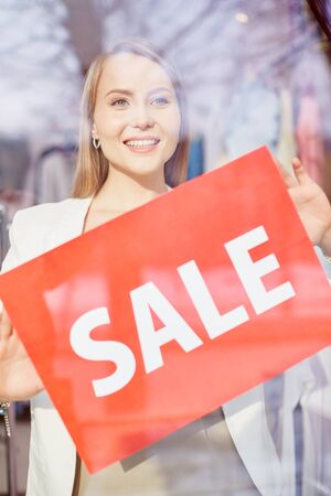 announcing: Beautiful young woman announcing season sale in boutique