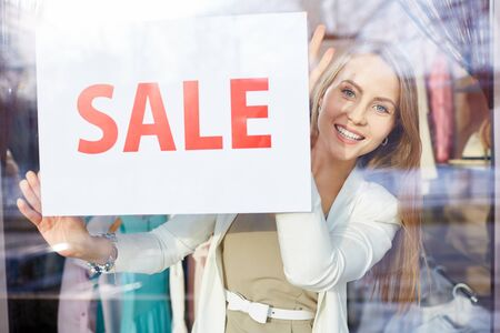 shopaholism: Beautiful young woman announcing sale in boutique Stock Photo