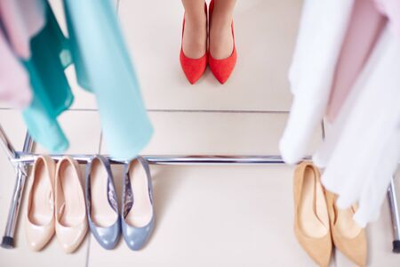 shopaholism: Row of stylish shoes and female feet in red ones Stock Photo