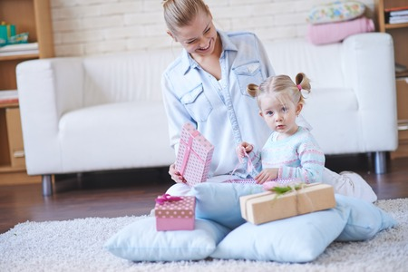 Happy woman looking at her little daughter unpacking giftbox photo