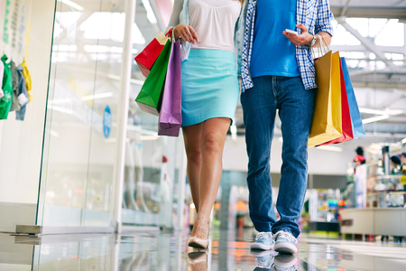 man shopping: Legs of young couple of shoppers walking down mall
