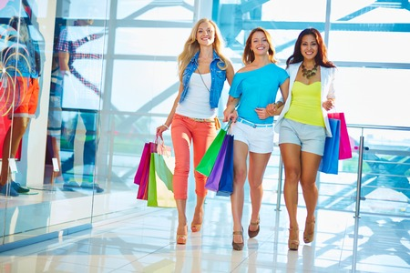 go shopping: Friendly consumers with paperbags walking down mall Stock Photo