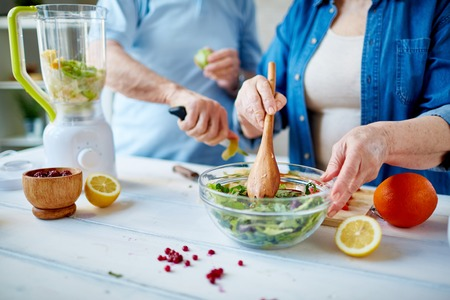 the mixing: Senior female mixing ingredients of vegetable salad Stock Photo