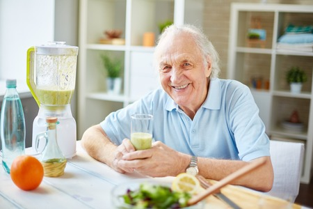 Senior man with glass of fruit smoothie looking at camera photo