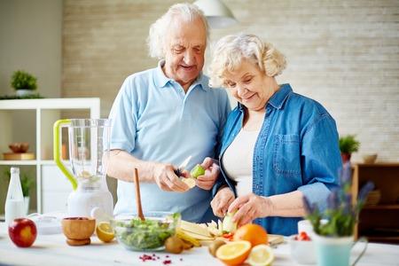senior lady: Modern senior couple preparing fresh fruits for making smoothie