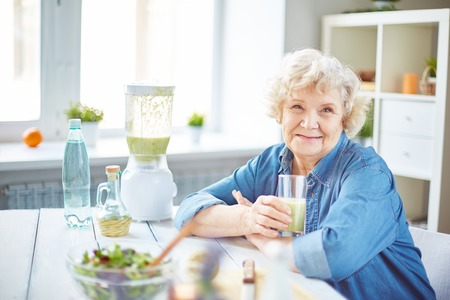 one senior: Happy senior female with glass of fruit smoothie looking at camera