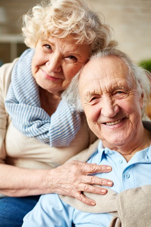 happy senior couple: Affectionate seniors looking at camera with smiles Stock Photo
