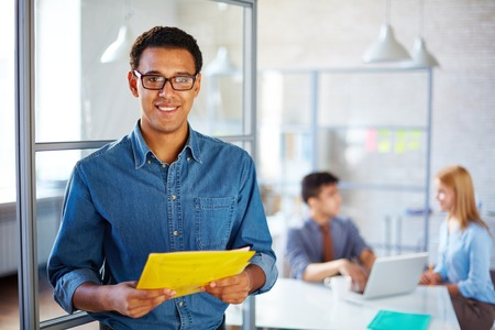 career young: Businessman with documents looking at camera in working environment