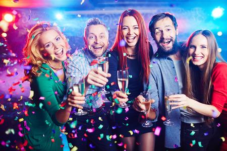 Jonge mensen met champagne fluiten in confetti
