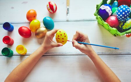 creative egg painting: Girl decorating Easter eggs