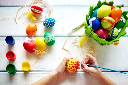 creative egg painting: Female hands painting Easter eggs