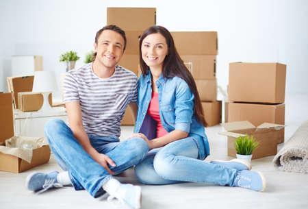 unpacked: Happy couple sitting among unpacked boxes Stock Photo