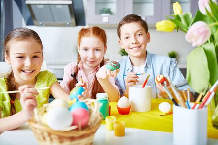 creative egg painting: Group of children painting Easter eggs Stock Photo