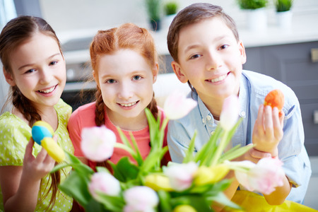 Portrait of three children with flowers and eggs photo