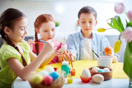 creative egg painting: Children painting eggs at school