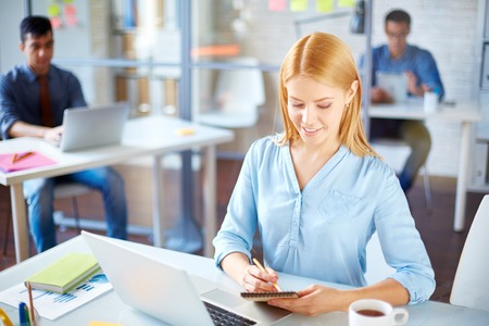 Young businesswoman looking through notes in office photo
